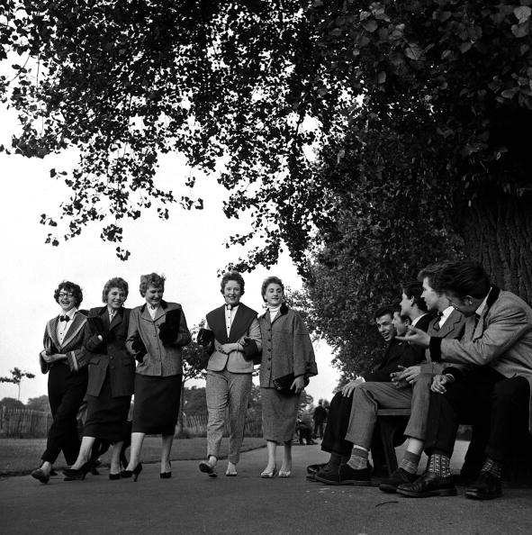 A group of Teddy Boys sitting on a park bench by a huge tree as they watch girls walking by, 1955 (Photo by Popperfoto/Getty Images)